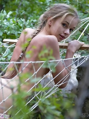 Blue-eyed cutie Milena D playfully posing on a hammock while showing off her nubile assets.